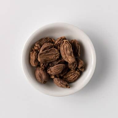 black cardamom pods in small white bowl