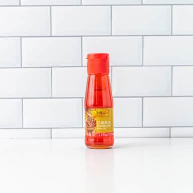 bottle of chili oil on white tabletop