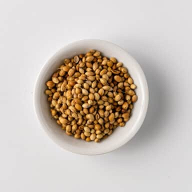 coriander seeds in small white bowl