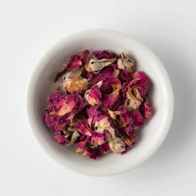 dried rose petals in small white bowl