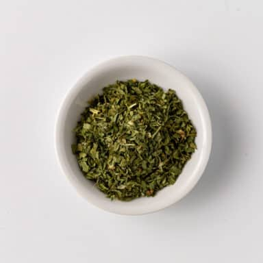 fenugreek leaves in small white bowl