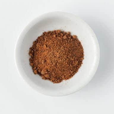 ground nutmeg in small white bowl