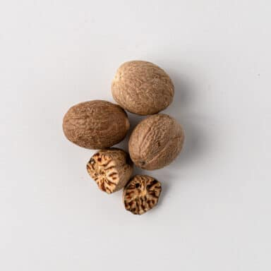 nutmeg seeds on white table top