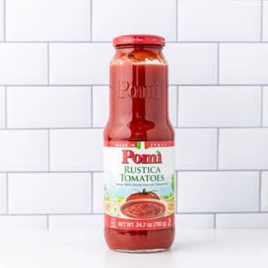 glass jar of tomato passata on white table top