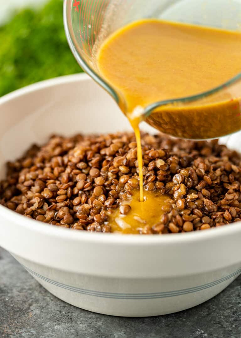 pouring mustard dressing onto cooked brown lentils