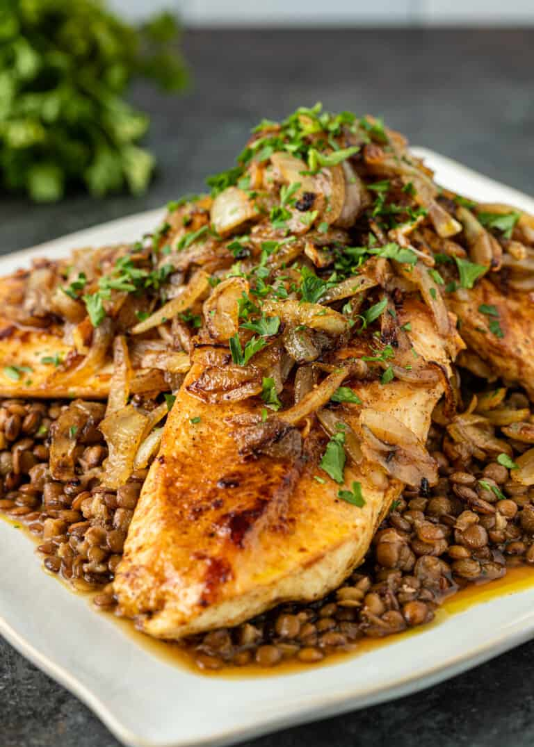 chicken and lentils with garnish of chopped parsley and sauteed onion