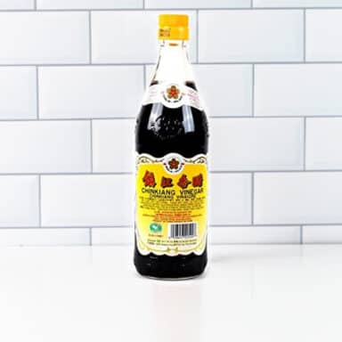 bottle of black rice vinegar on white table top