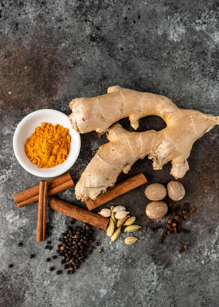 whole spices and ginger root with bowl of turmeric