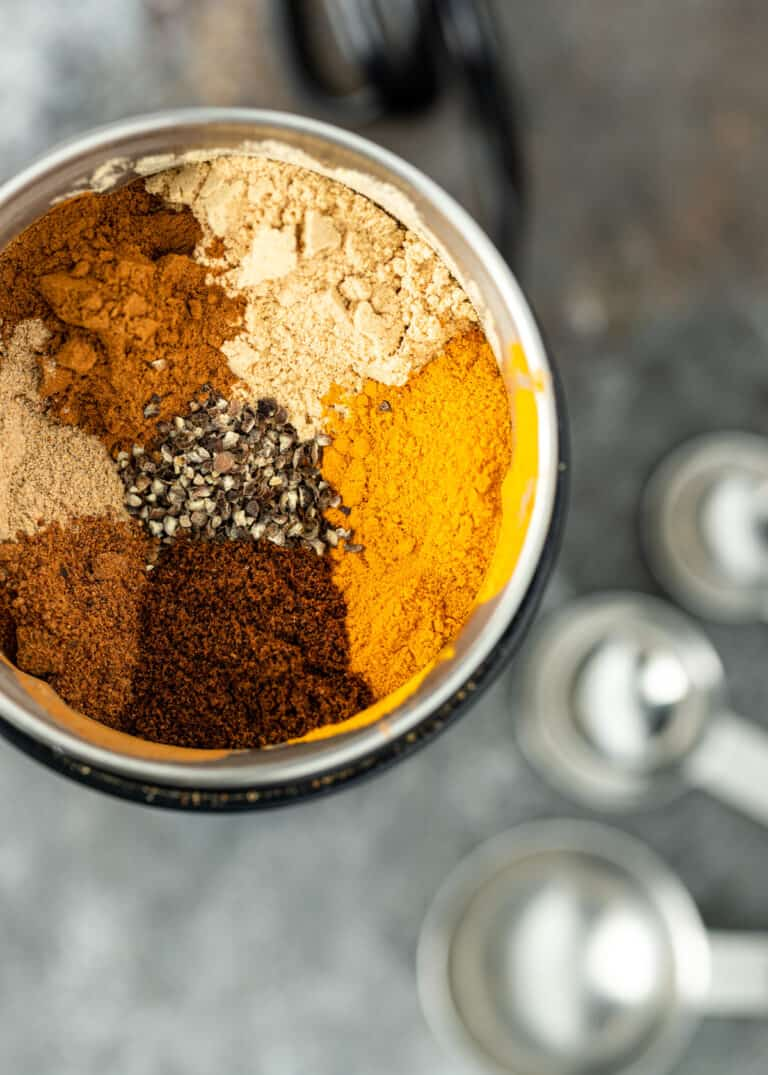 Moroccan seven spice blend in a spice grinder with measuring spoons in background