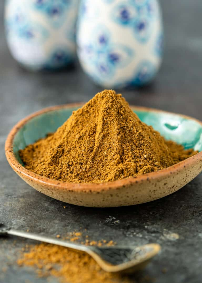 Moroccan seven spice piled high in blue dish with spoon