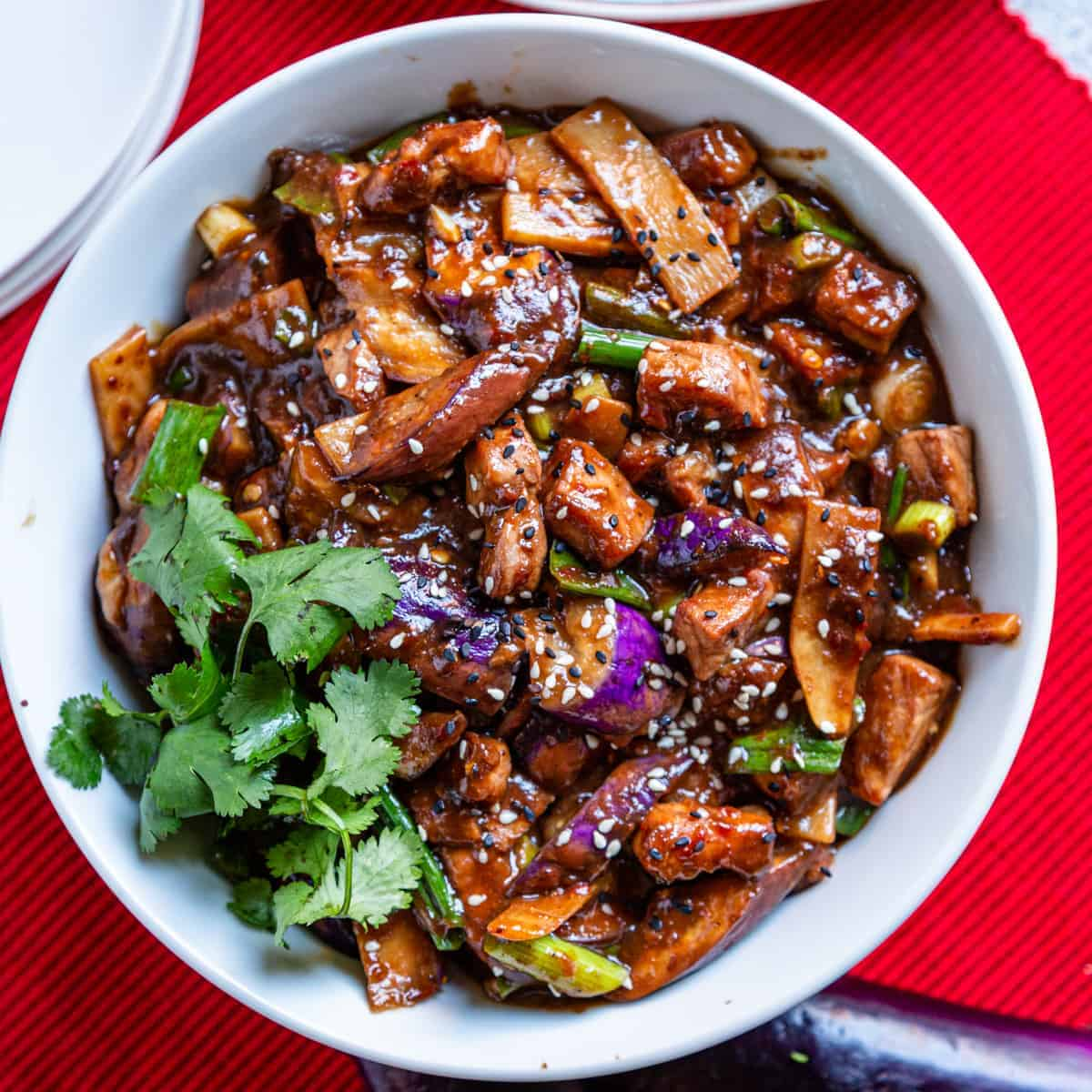 overhead photo of Szechuan Eggplant and Pork Stir Fry in bowl on red placemat