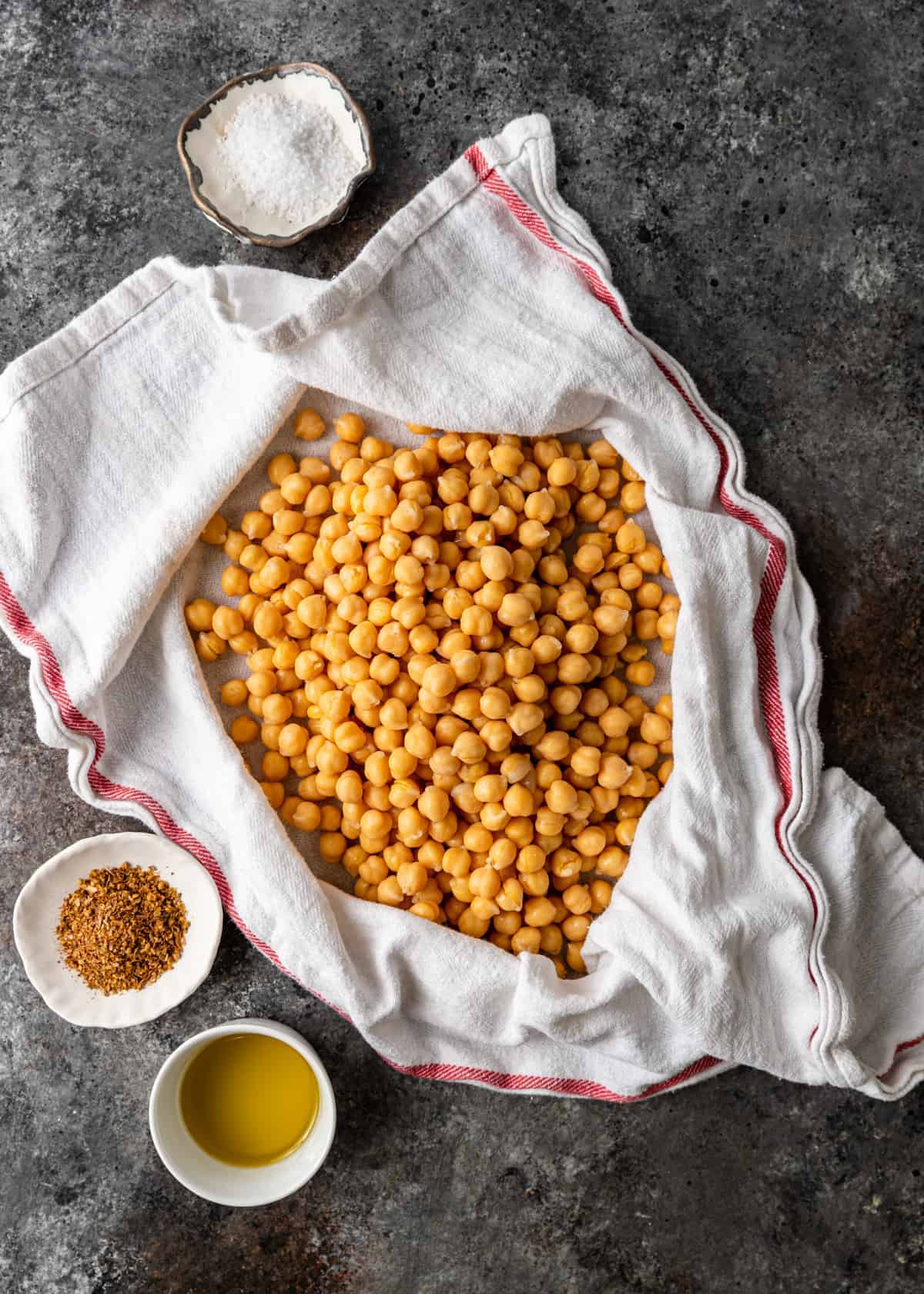 overhead image of ingredients for turkish roasted chickpeas: chickpeas, olive oil, sugar, and a spice blend.