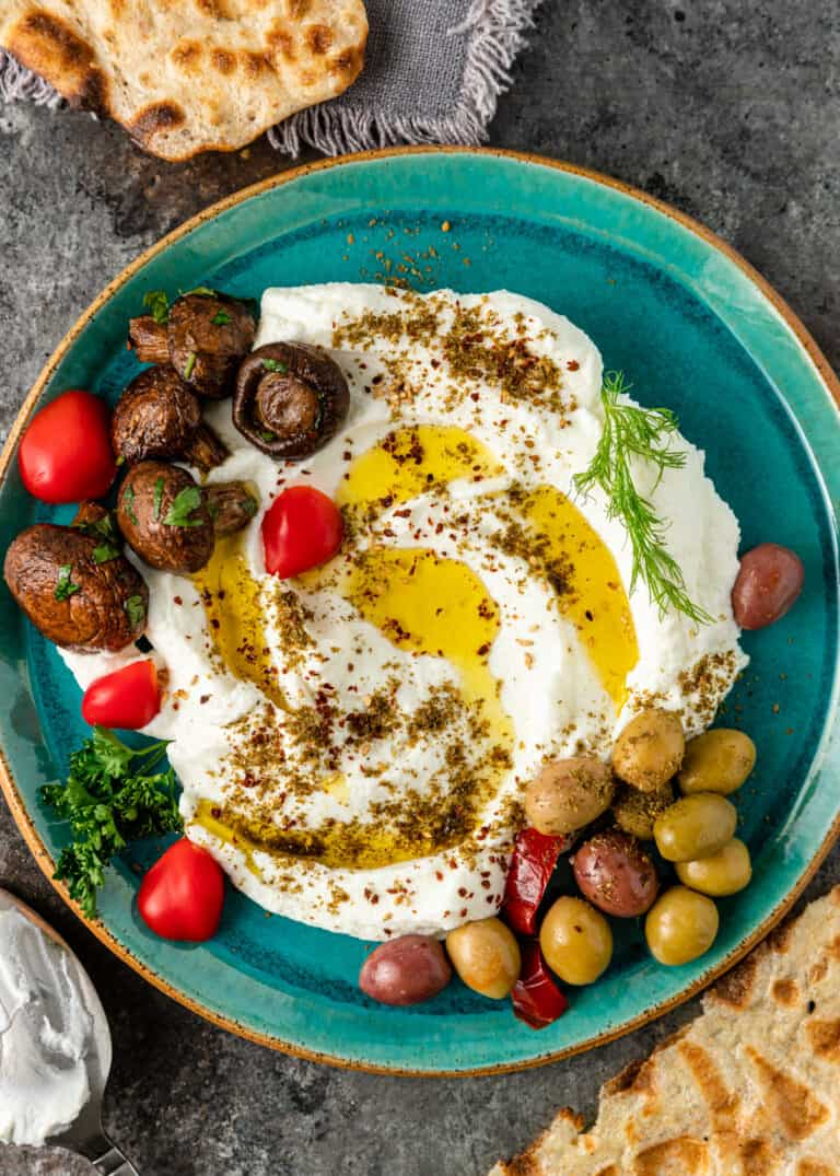 platter of homemade labneh with marinated mushrooms, olives, and cherry tomatoes