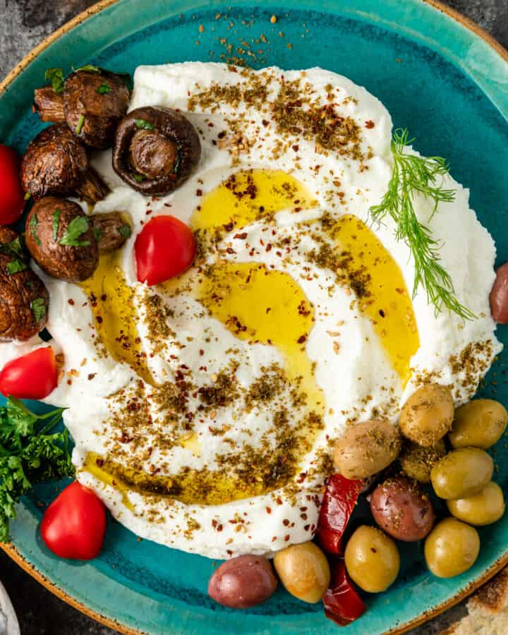 homemade labneh in aqua colored dish, topped with olive oil and marinated vegetables