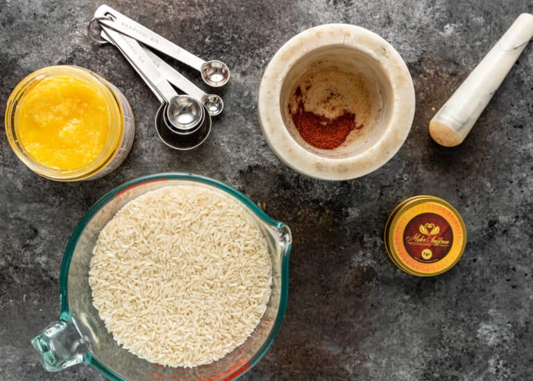 overhead image of ingredients and a mortar and pestle for making Persian rice tahdig recipe
