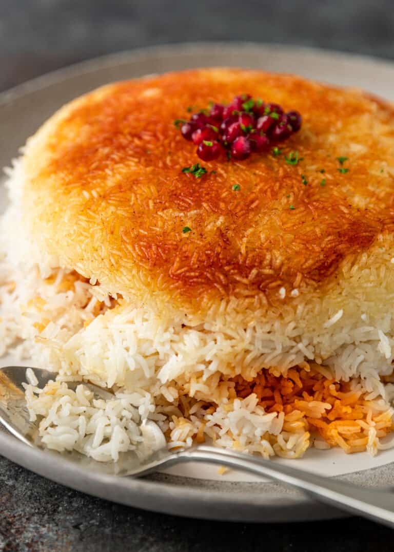 plated dish of tahdig rice garnished with pomegranate arils