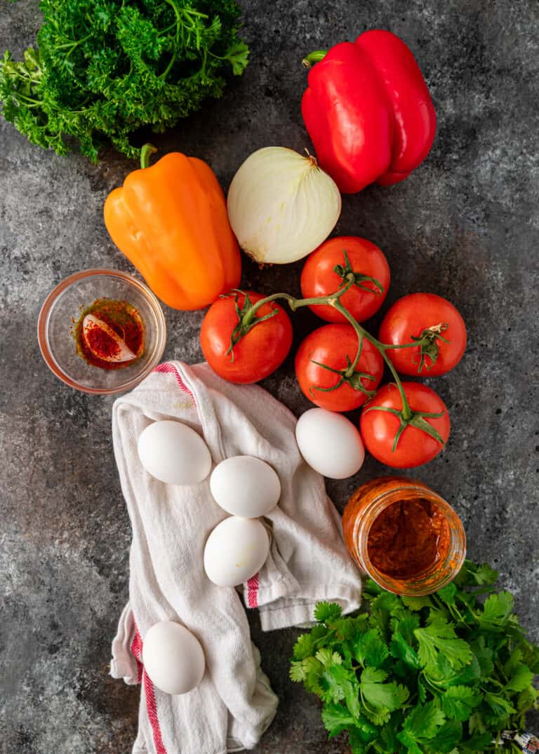 whole eggs, fresh tomatoes, colored bell peppers and other ingredients for making a shakshuka recipe