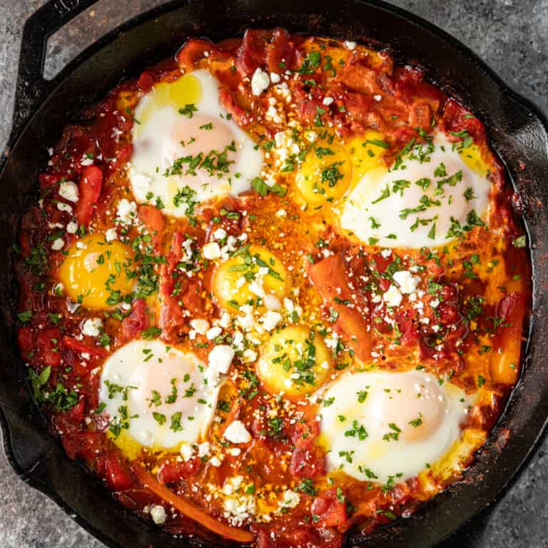 skillet of poached eggs in spicy tomato sauce