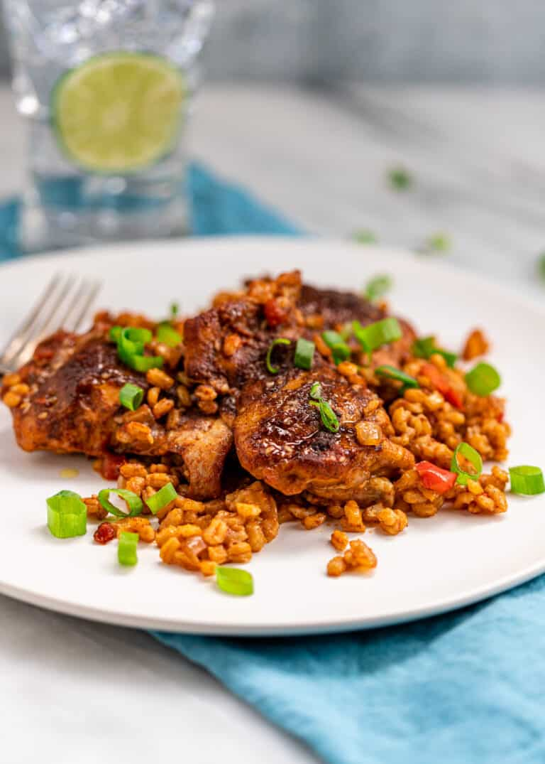 side view: North African chicken plated on a bed of pearled barley