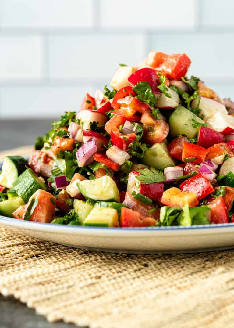 side view: diced tomatoes, cucumber and onion piled high on a plate