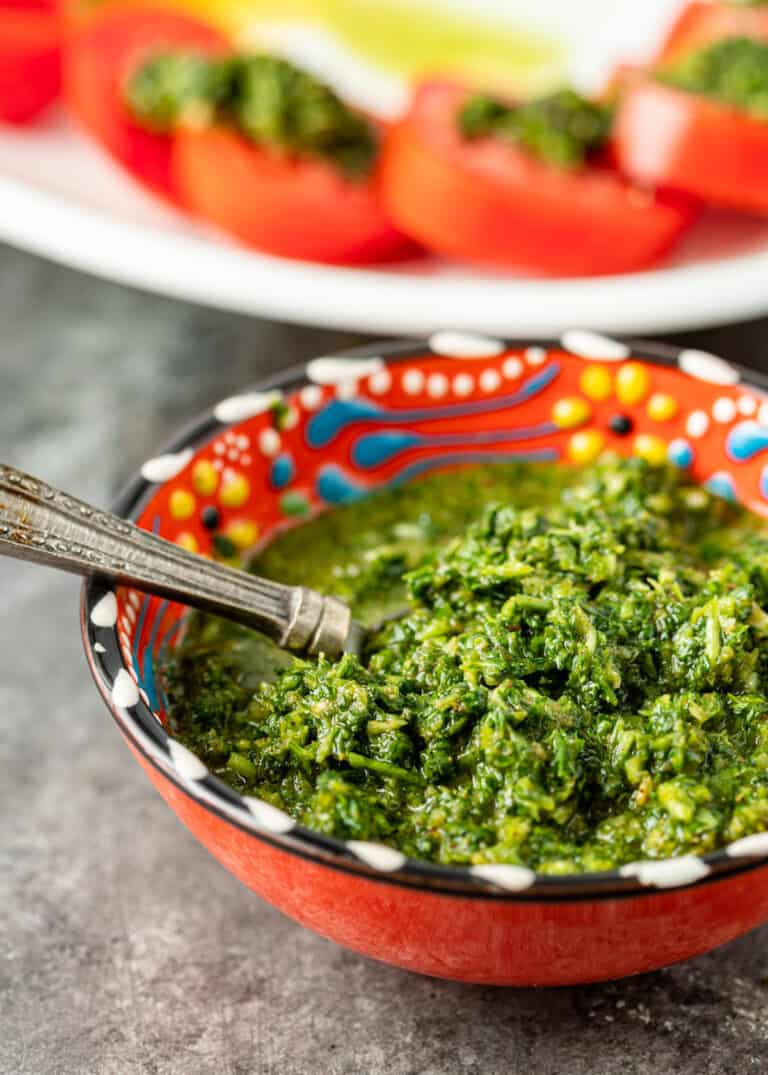 spoon in bowl of Lebanese green hot sauce with plate of tomato slices in background