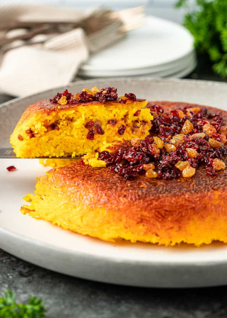 side view: serving spatula lifting wedge of baked saffron rice cake away from the rest of the cake