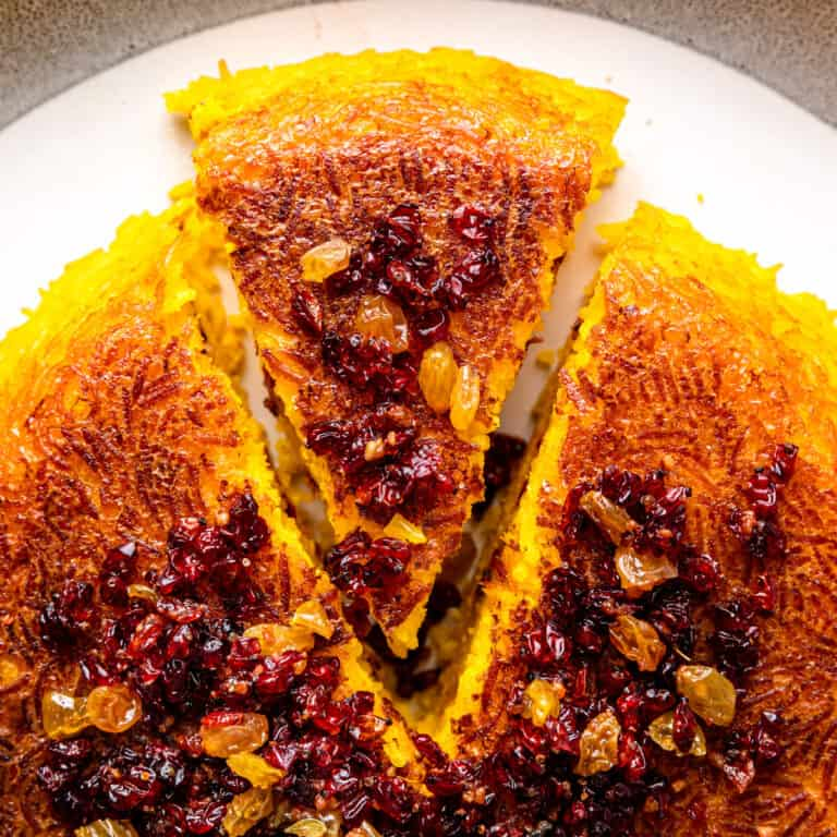 overhead image: wedge of baked tachin topped with dried barberries and golden raisins