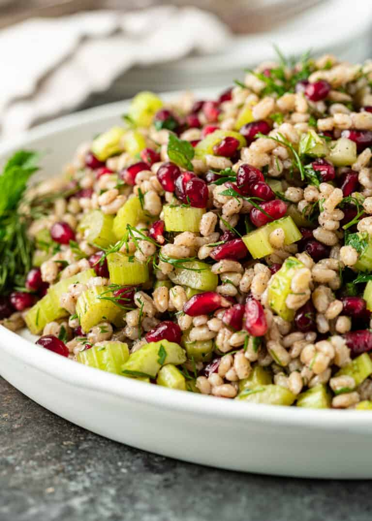 close up of pearl barley with celery, garlic, herbs, and pomegranate seeds in delicious homemade dressing