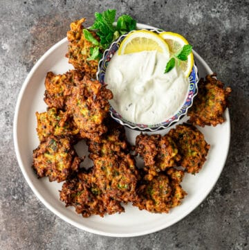 overhead: middle eastern side dish: fried vegetable patties with bowl of mint yogurt sauce for dipping