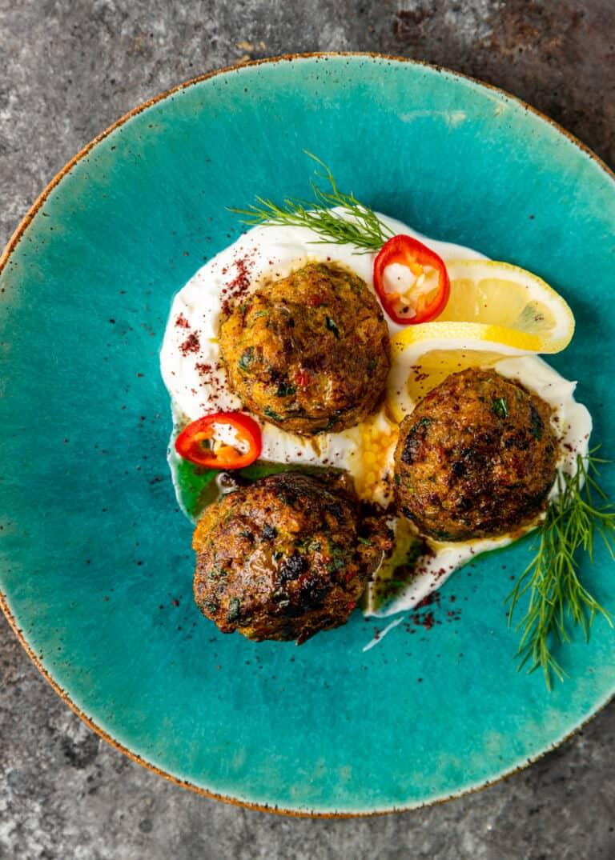 overhead: 3 kofta meatballs on blue plate with sprinkling of sumac