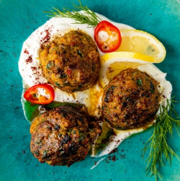 overhead: 3 fish meatballs sitting in homemade labneh on a blue plate