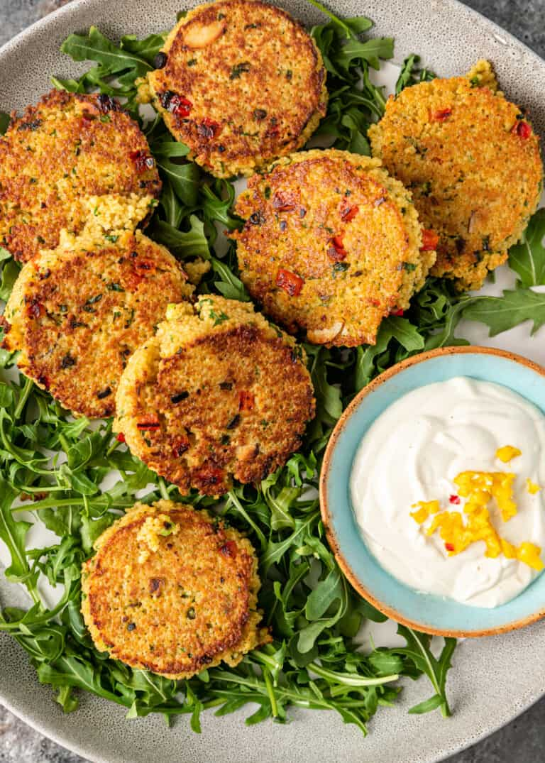 overhead image: Moroccan vegetable couscous cakes on platter with dish of labneh