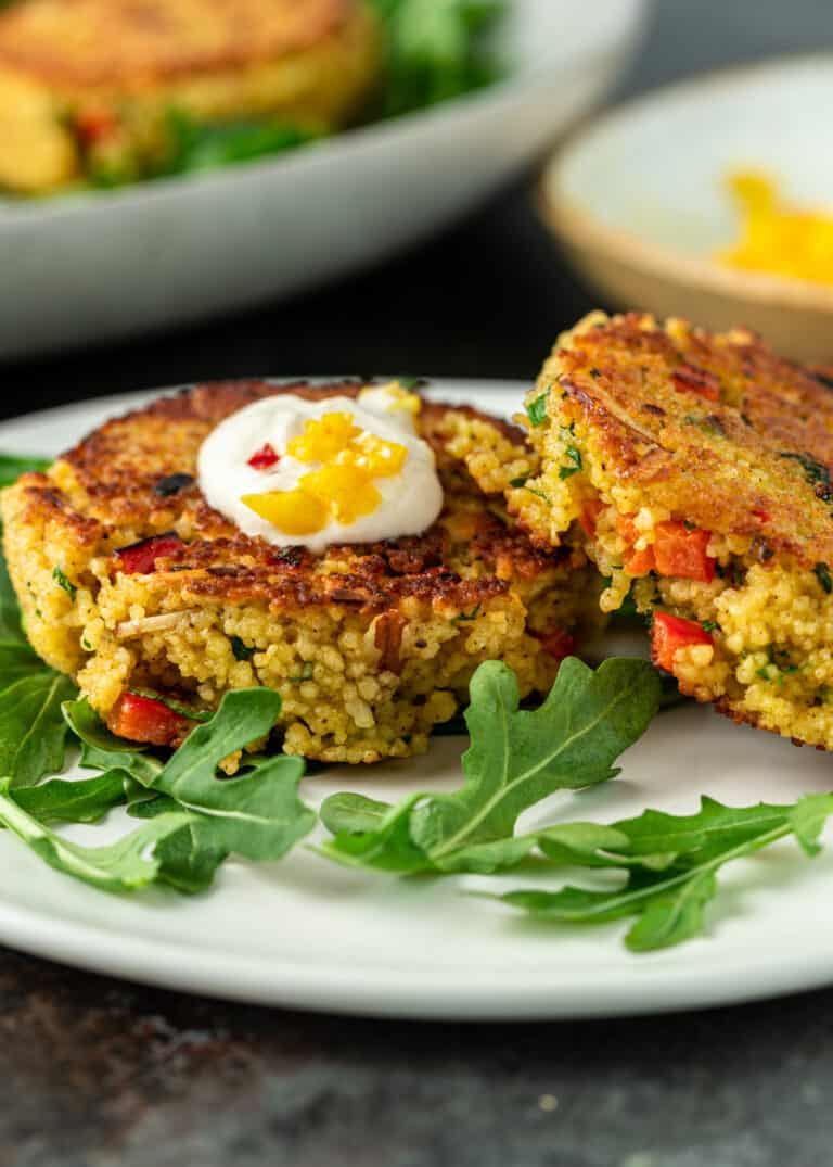 side view: two Moroccan vegetable couscous cakes topped with labneh on small white plate