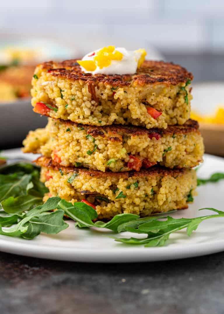 three fried couscous patties stacked on small white plate garnished with fresh arugula