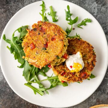 overhead closeup photo: two Moroccan vegetable couscous cakes on arugula sit on white serving plate