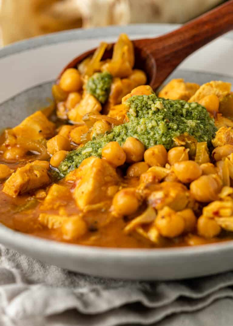 closeup image of chicken and chickpea stew with a large wooden spoon