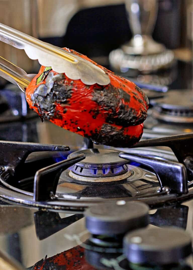 charred red bell pepper over open flame on stovetop
