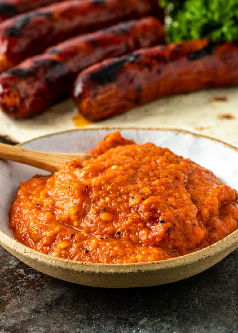 Serbian roasted red pepper ajvar relish in a bowl with grilled Serbian sausage in the background
