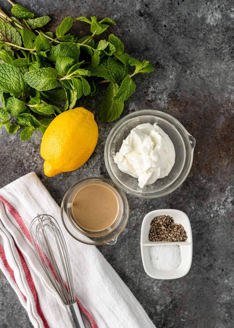 overhead image: bowl of Greek yogurt, whole fresh lemon, fresh mint, tahini paste, and salt and pepper, all on a gray backdrop with a whisk and kitchen towel