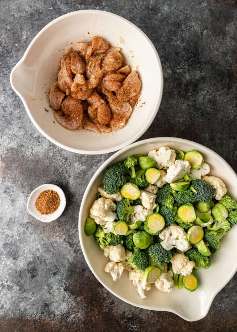 overhead: 2 white mixing bowls with raw vegetables and Turkish spiced chicken tenders