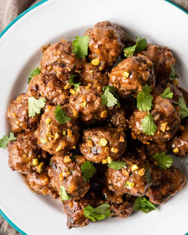 overhead: homemade lamb meatballs on a white plate