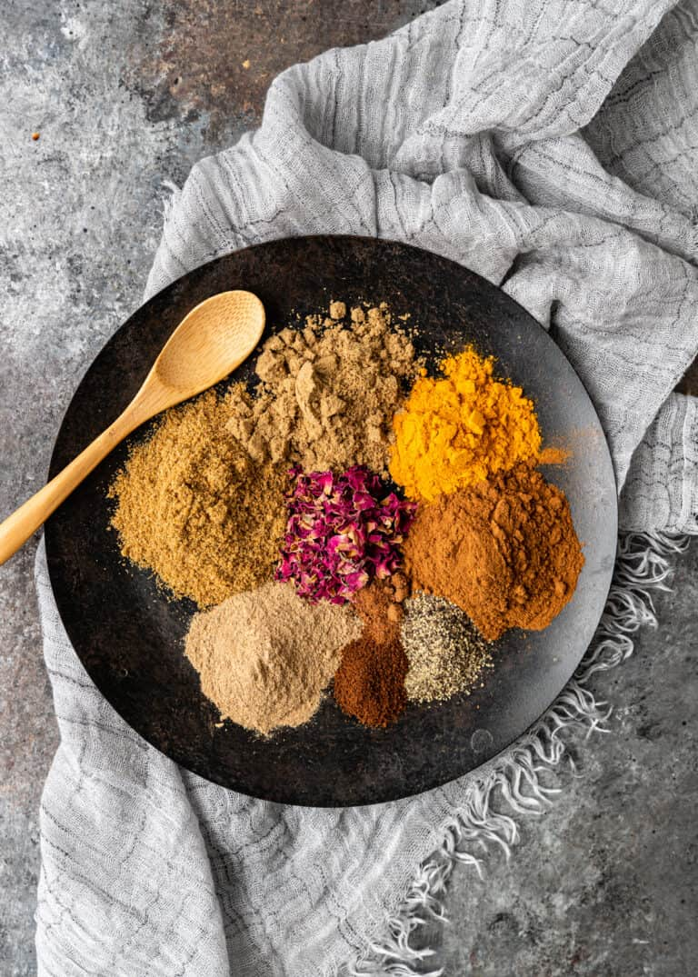 overhead: 8 small piles of ground Persian spices on black plate for advieh Persian spice mix