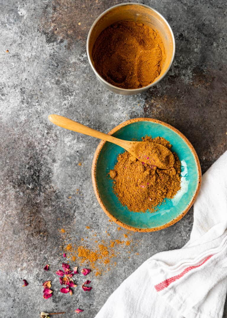Persian spice mix in small glazed pottery bowl with wooden spoon
