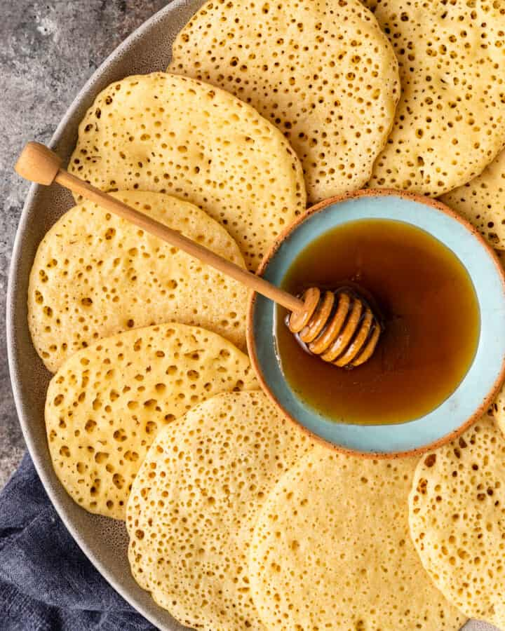 close up overhead image: platter of semolina pancakes arranged around a bowl of honey