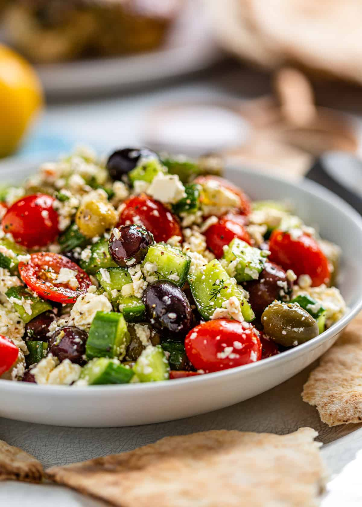 plate of healthy Mediterranean salad with olives, tomatoes, and crumbled cheese