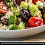 titled Pinterest image shows side view of Greek Feta Salad on white plate