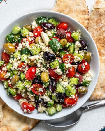 overhead image: pita bread surrounds Greek feta salad on white plate