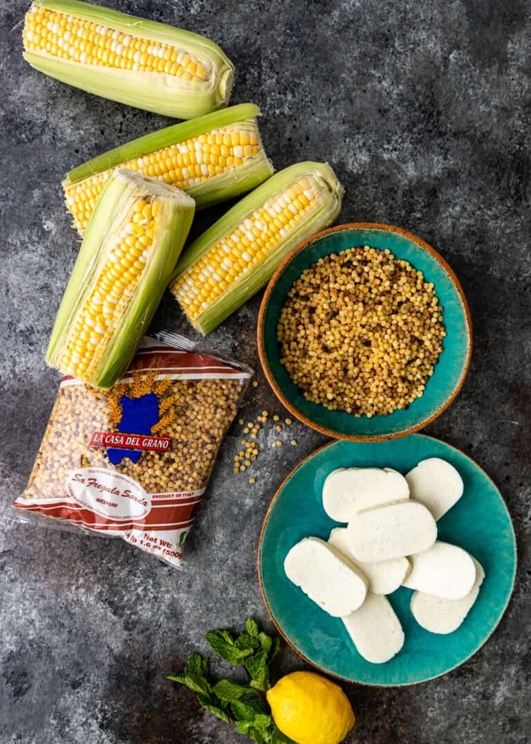 uncooked ears of corn on the cob, bowl of uncooked fregola pasta and small plate with slices of halloumi cheese