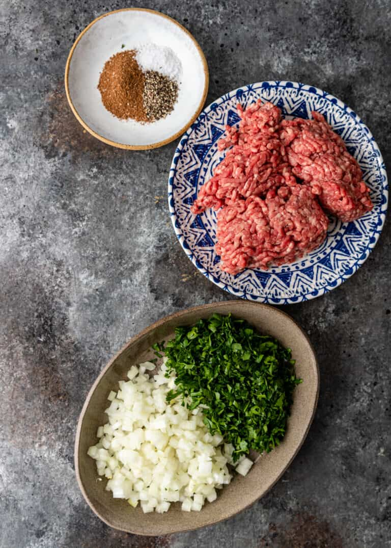 overhead image: plate of ground meat, dish of Lebanese 7 spice and bowl of diced onion and chopped parsley