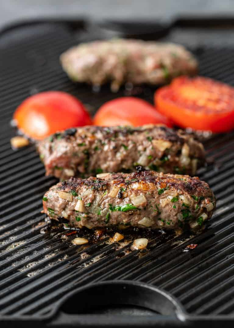 ground beef (in log shapes) cooking on grill with tomatoes